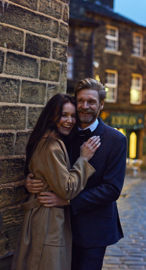 A smiling couple standing on a street corner in the historic village of Haworth in West Yorkshire, embracing.